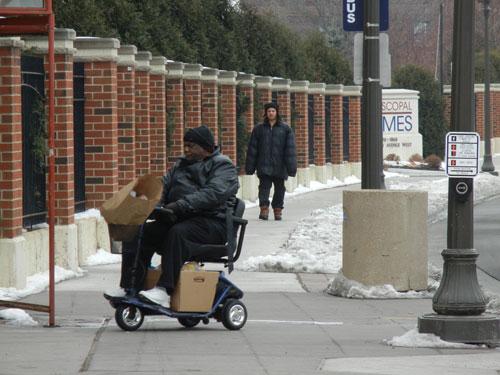 2-men-on-university-avenue-sidealk-in-saint-paul-one-walking-one-using-motorized-wheelchair
