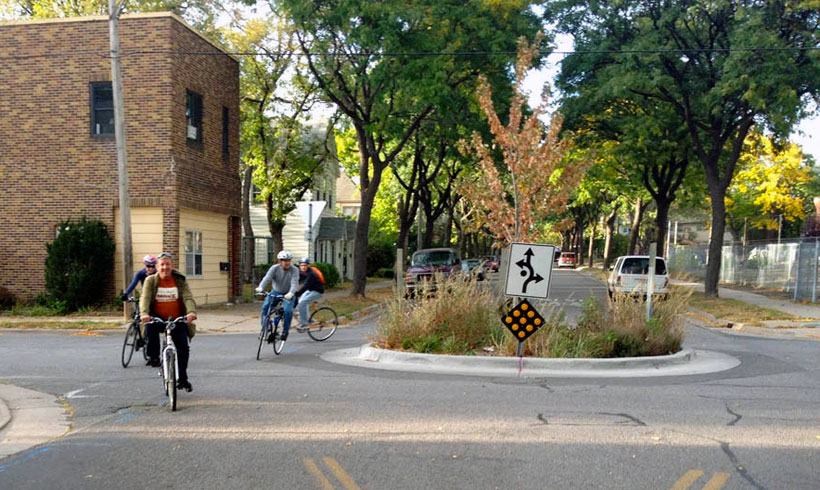 four-bicyclists-ride-around-traffic-circle-on-fifth-street-bicycle-boulevard-in-northeast-minneapolis